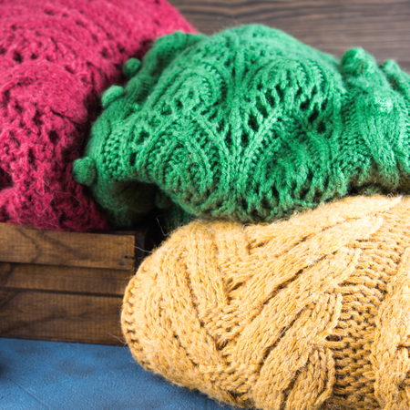 womans clothing: Winter womans woolen sweaters. Knitted girls clothing. Colorful pullovers on wooden background. Cozy clothes for the season. Square image