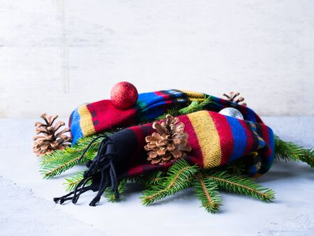 pinecones: Fir tree branches in woolen scarf with pine cones and Christmas baubles. Winter symbols still life Stock Photo