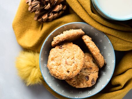 pinecones: Mug of tea with milk and cookies with chocolate chips in a soft yellow winter scarf on gray background. Coffee break for home relax. Top view