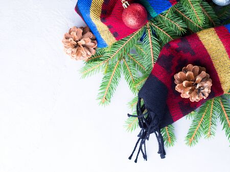 Fir tree branches in woolen scarf with pine cones and Christmas baubles. Winter symbols still life top view Stock Photo