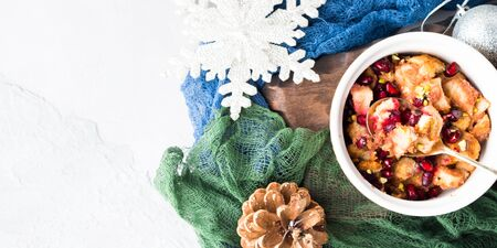 Christmas baked apple dessert with pomegranate seeds. Winter holidays treat on textured background. Overhead view. Banner