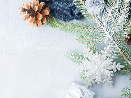 Christmas winter gray background with fir tree branches, pine cones, baubles and snow. New year greeting card in cold colors.