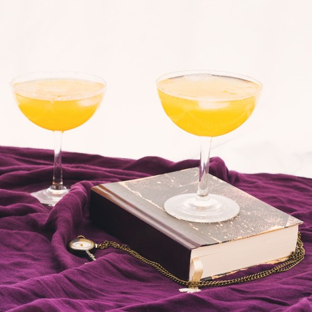 Two orange alcohol cocktails on purple textile with a book