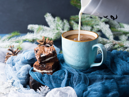 Cream cheese brownies with cookies on blue mug of coffee and milk being poured. Winter treat square chocolate bars. Holiday background with fir tree branches and baubles Stockfoto