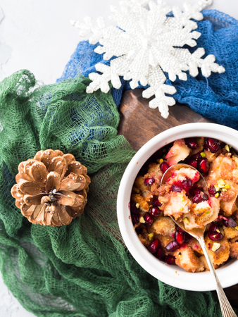 Christmas baked apple dessert with pomegranate seeds. Winter holidays treat on textured background. Overhead view