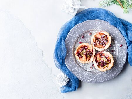 Christmas baked mini apple shortcrust pies with pomegranate seeds. Winter holidays treat on textured background. Simple new year dessert. Overhead view
