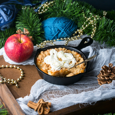 Apple fruit crumble with cream as Christmas home made dessert. Festive treat served in cast iron skillet. Winter decorations and colors. Sweet food still life on dark background.