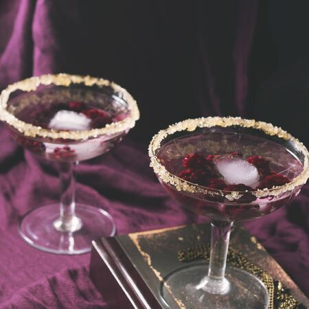 Two aperitif alcohol cocktails drinks with berries on purple background for romantic date. Square toned