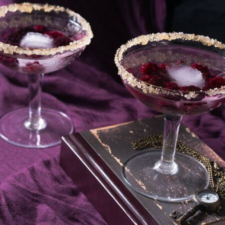 Two aperitif alcohol cocktails drinks with berries on purple background for romantic date. Square Stock Photo