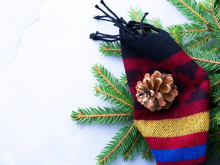 Fir tree branches in woolen scarf with pine cones and Christmas baubles. Winter symbols still life Stock Photo