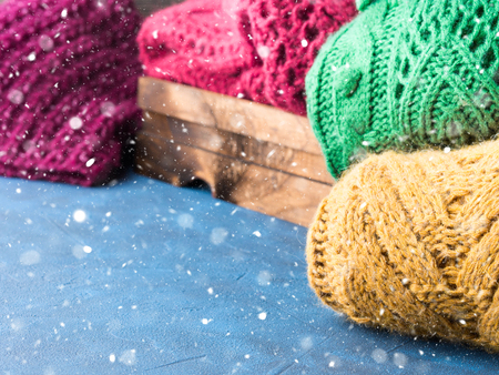 Winter womans woolen sweaters. Knitted girls clothing. Colorful pullovers on wooden background. Cozy clothes for the season. Copy space Stock Photo