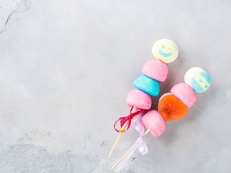 Colorful marshmallows cake pops on wooden sticks with smiling faces together. Valentines day card or childrens party. Copy space. Sweet food treat