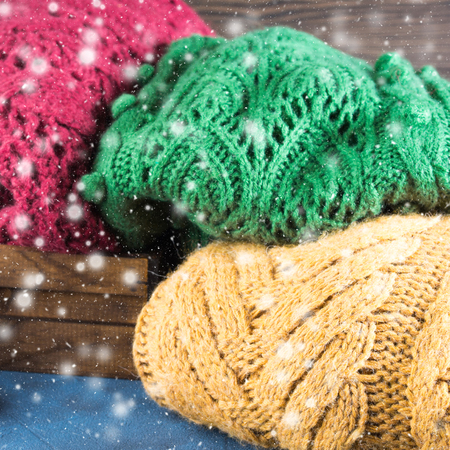 pullovers: Winter womans woolen sweaters. Knitted girls clothing. Colorful pullovers on wooden background. Cozy clothes for the season. Square image. Falling snow effect Stock Photo
