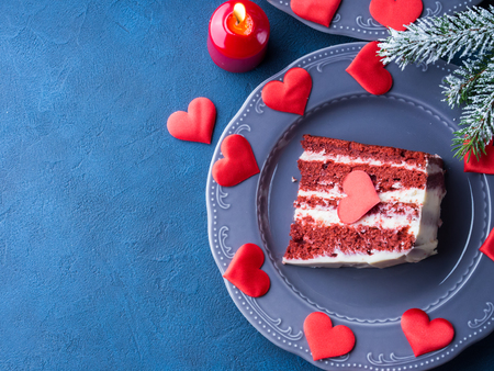 Red velvet cake slice for Valentines day dessert. Sweet treat for romantic date or Christmas party. Holiday celebration dark blue and black background with winter fir tree branches.