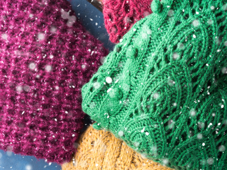 pullovers: Winter womans woolen sweaters. Knitted girls clothing. Colorful pullovers on wooden background. Cozy clothes for the season. Top view