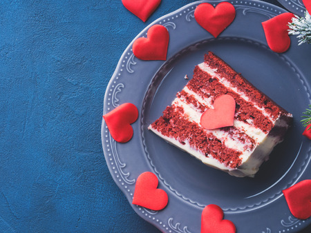 bougie coeur: Red velvet cake slice for Valentines day dessert. Sweet treat for romantic date or Christmas party. Holiday celebration dark blue and black background with winter fir tree branches.
