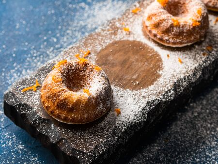 napkin ring: Small bundt ring cakes with orange zest icing sugar on dark blue background and serving board. Holiday sweet food Stock Photo
