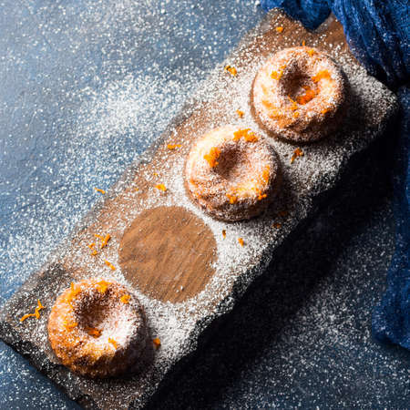 napkin ring: Mini bundt ring cakes with orange zest icing sugar on dark blue background and serving board. Top view. Holiday christmas sweet food