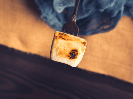 Порно: Smoked marshmallow on vintage fork on dark background. Toned top view burlap Фото со стока