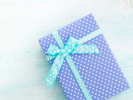 Blue gift box with ribbon on pastel background. Copy space top view fathers day Christmas special occasion present