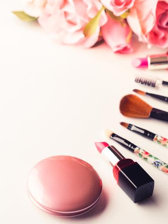 메이크업 제품 립스틱, 홍당무 및 흰색 배경에 핑크 장미 꽃과 도구 브러쉬. 라이프 스타일 여자 정물