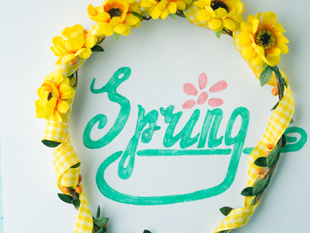 Spring word spelling by hand lettering and flower wreath girl head band. Flat lay season mood Stock Photo