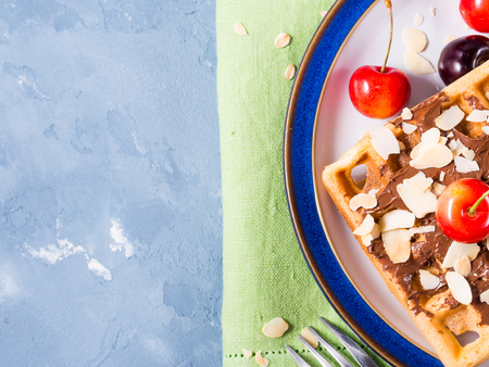 made in belgium: Sweet treat belgian waffles with chocolate almond shreds and cherries on blue textured background