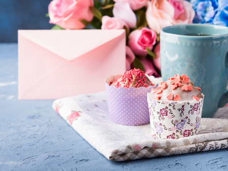 Mothers day Valentine concept muffins with hearts sprinkles and cup of tea on napkin. Flowers