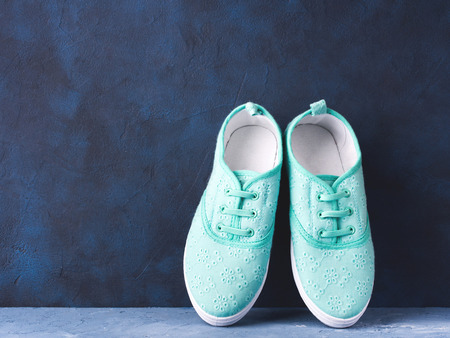 Pair of green pastel woman girl child canvas tennis sneakers on blue textured background