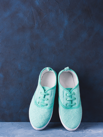 shoelace: Pair of green pastel woman girl child canvas tennis sneakers on blue textured background