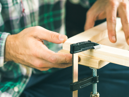 Mens die houten stoelvoorwerp bewerken houten raad in handen houden. Doe het zelf projectmakingsproces. Persklem gebruiken