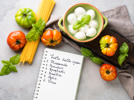 Pasta, tomato, mozzarella still life on gray rustic background. Traditional products and food shopping list for spaghetti with tomatoes in Italian