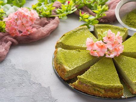 Matcha baked cheese cake and pink flowers on gray concrete background Stock Photo