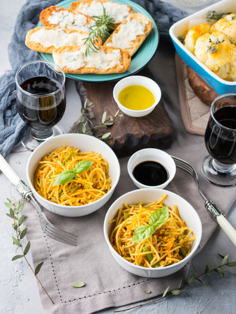 bean family: Lunch with curry pasta noodles in bowls and vegetables with turmeric