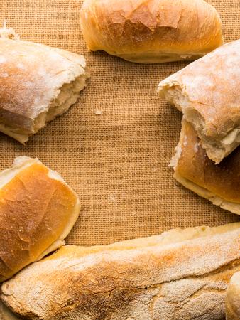 Vers gebakken broodbroden op jute donkere houten achtergrond. Italiaanse de bakkerijproducten van de textuurclose-up