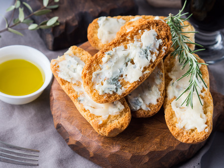 Italian toasts with gorgonzola cheese on rustic background with wine Stock Photo