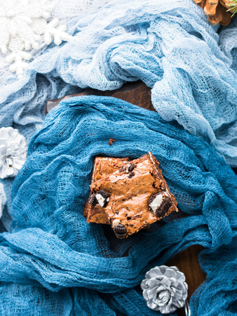 Cream cheese brownies with cookies on blue. Winter christmas treat square chocolate bars. Stock Photo