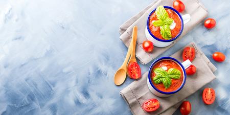 Creamy Tomato soup in enamel mugs on blue background Stock Photo