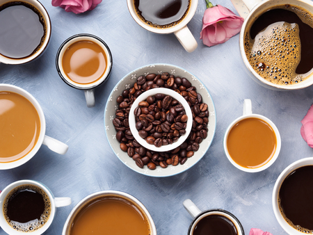 long bean: Cups and mugs of coffee and flowers on blue background Stock Photo
