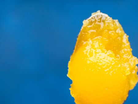 Organic yellow honey on silver spoon on blue background Stock Photo