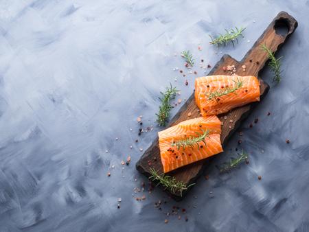 Piezas de salmón crudo en tablero de madera con hierbas, sal y especias Foto de archivo - 87951718