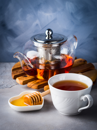 Cup of red tea rooibos and honey with glass teapot on blue