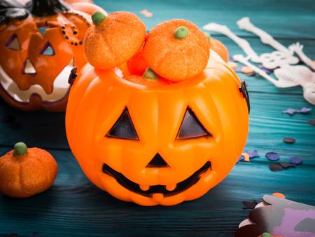 Halloween trick or treat still life on dark green. Toy pumpkin, sweets, marshmalllow, confetti. Holiday mood background Stock Photo