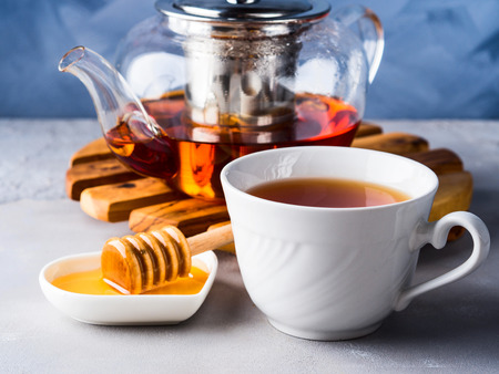 rooibos: Cup of red tea rooibos and honey with glass teapot on blue