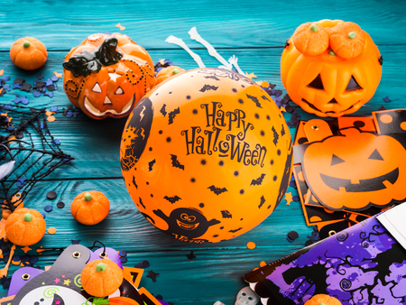 Halloween decoration symbols on dark rustic wooden background. Wishing happy holiday with orange balloon