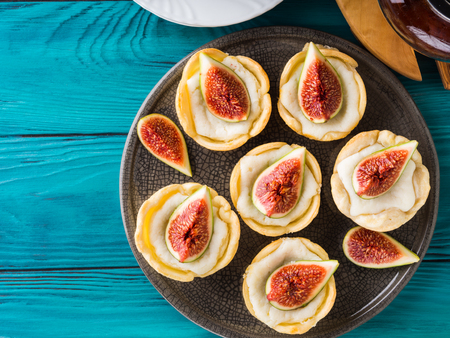 Tartlets with ricotta and figs on green wooden table. Mini treats Stock Photo
