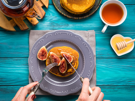 woman's hands: Eating pumpkin pancakes with figs and honey with hot tea. Autumn food background on green wooden table. Womans hands