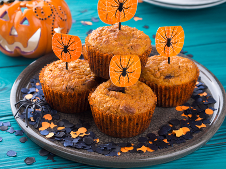 Pumpkin muffins with chocolate chips for Halloween kids party. Holiday decorations Stock Photo