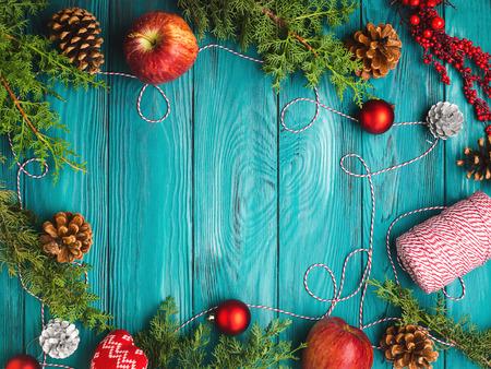 Vánoční tmavě zelené rám pozadí s borovice kužele, červené cetky a motouzy, jablka. Textura dřevěného stolu
