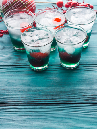 Christmas holiday party background with green alcohol drinks with cherry. Festive aperitif shots and ornaments on wooden dark table Stock Photo